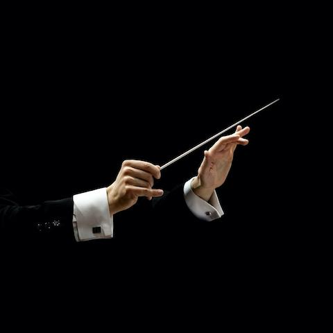 Hands of musical conductor holding a baton
